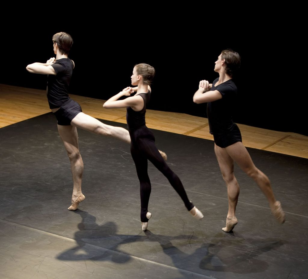 three dancers rehearsing on stage