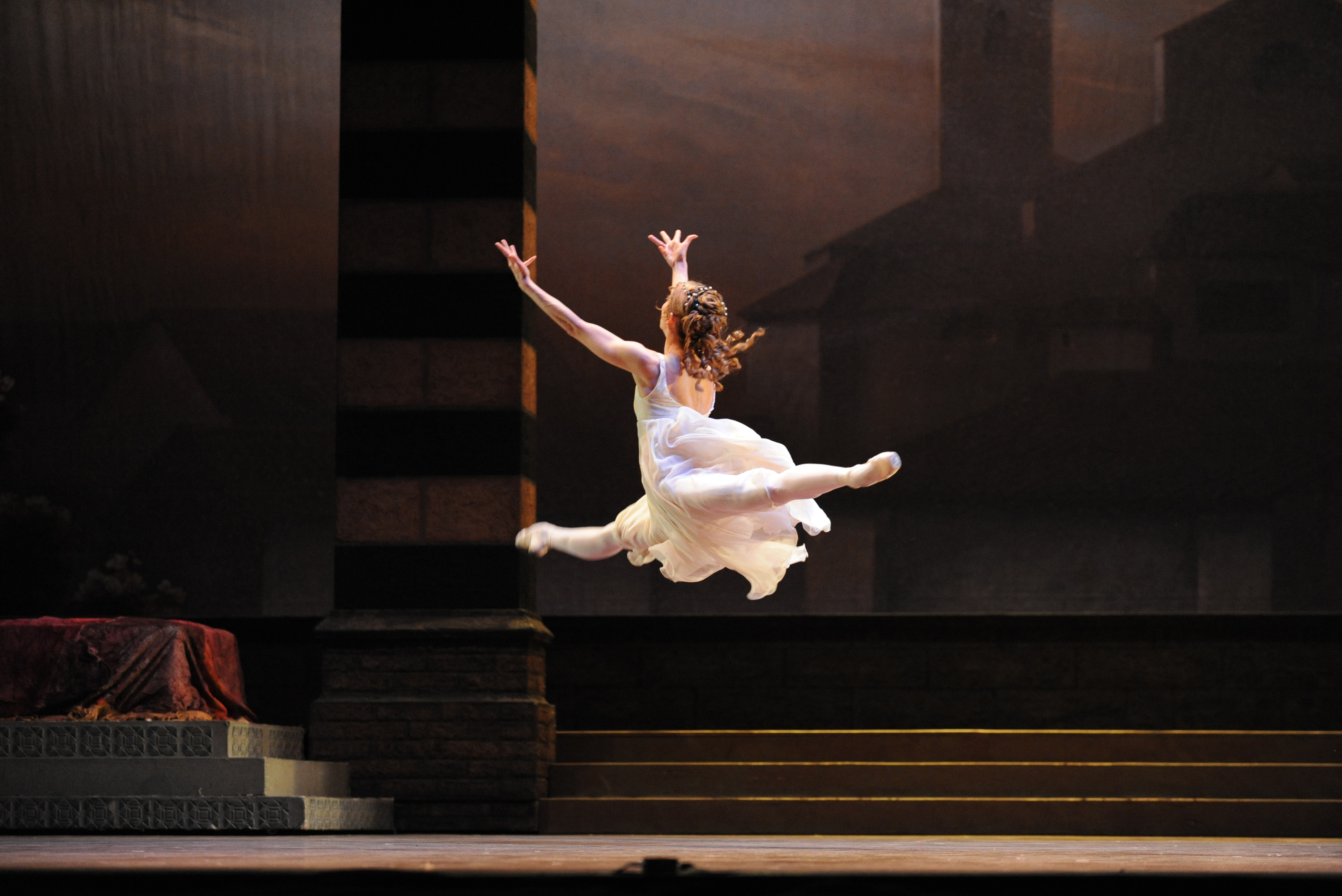 a ballet dancer jetes across the stage