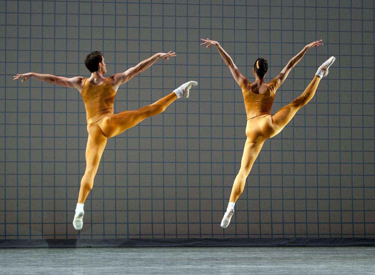 two dancers jumping, wearing orange