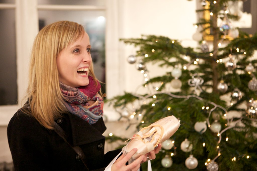 lady with pointe shoes stands in front of Christmas tree