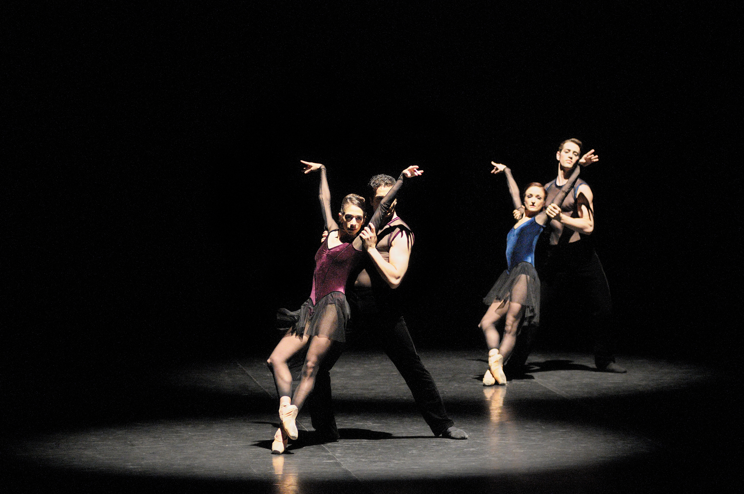 four dancers on stage in leotards