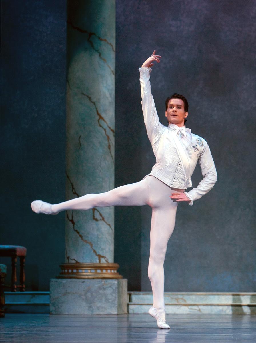 dancer in white in arabesque on stage