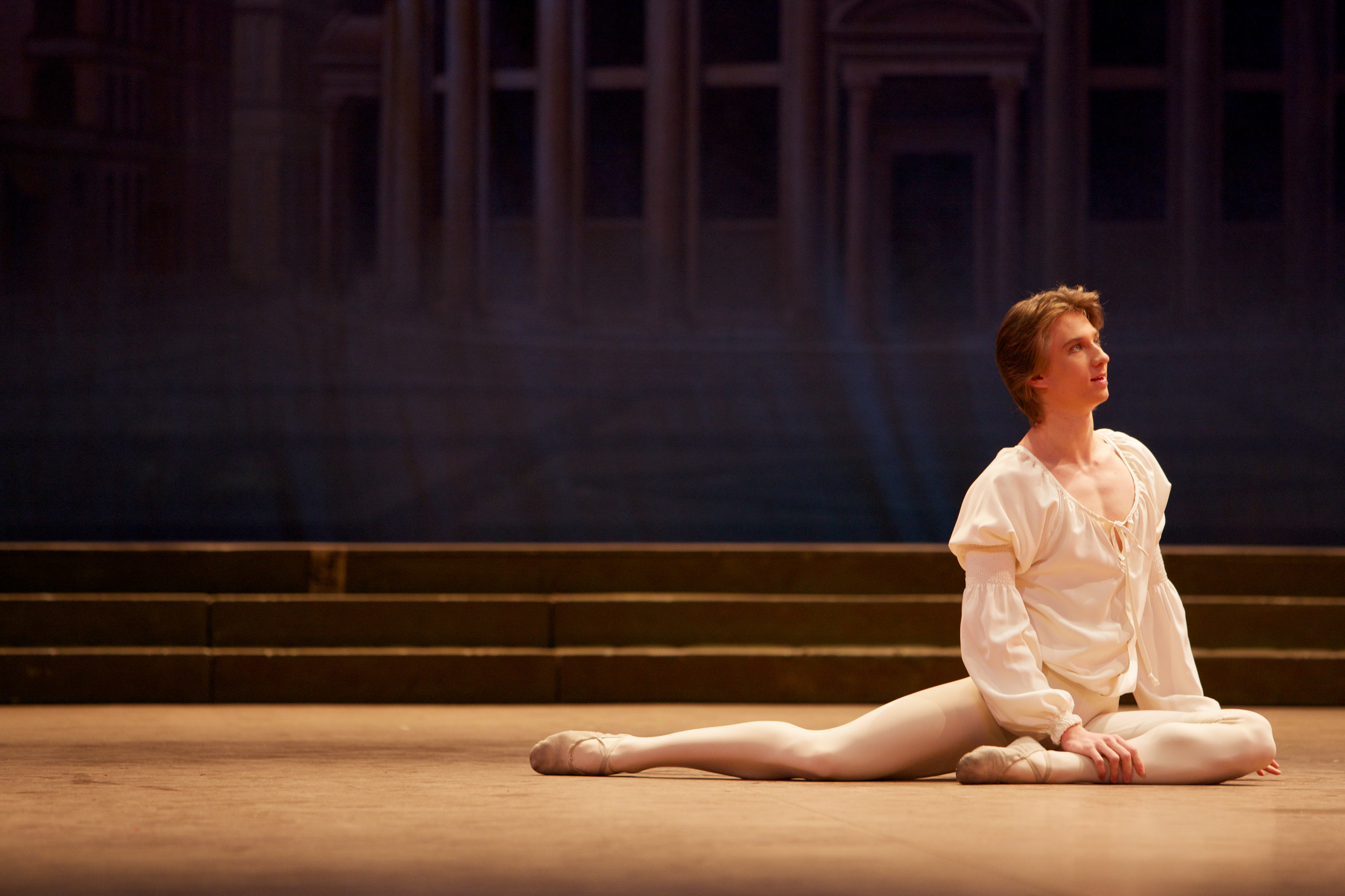 one ballet dancer sits alone on stage