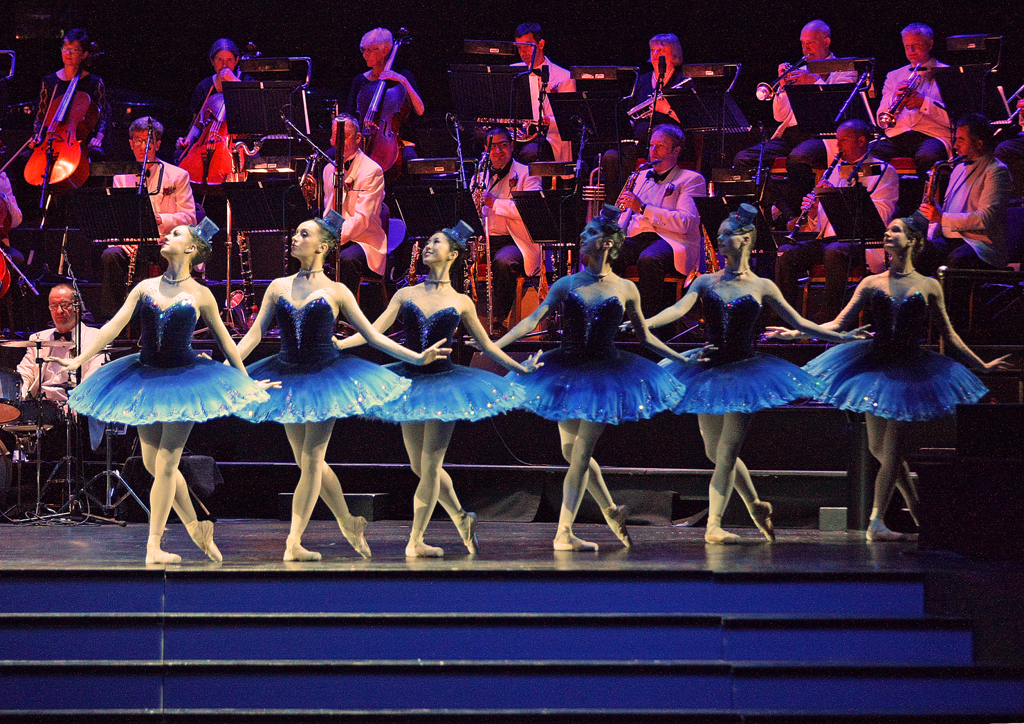 ballet dancers in a row wearing blue tutus