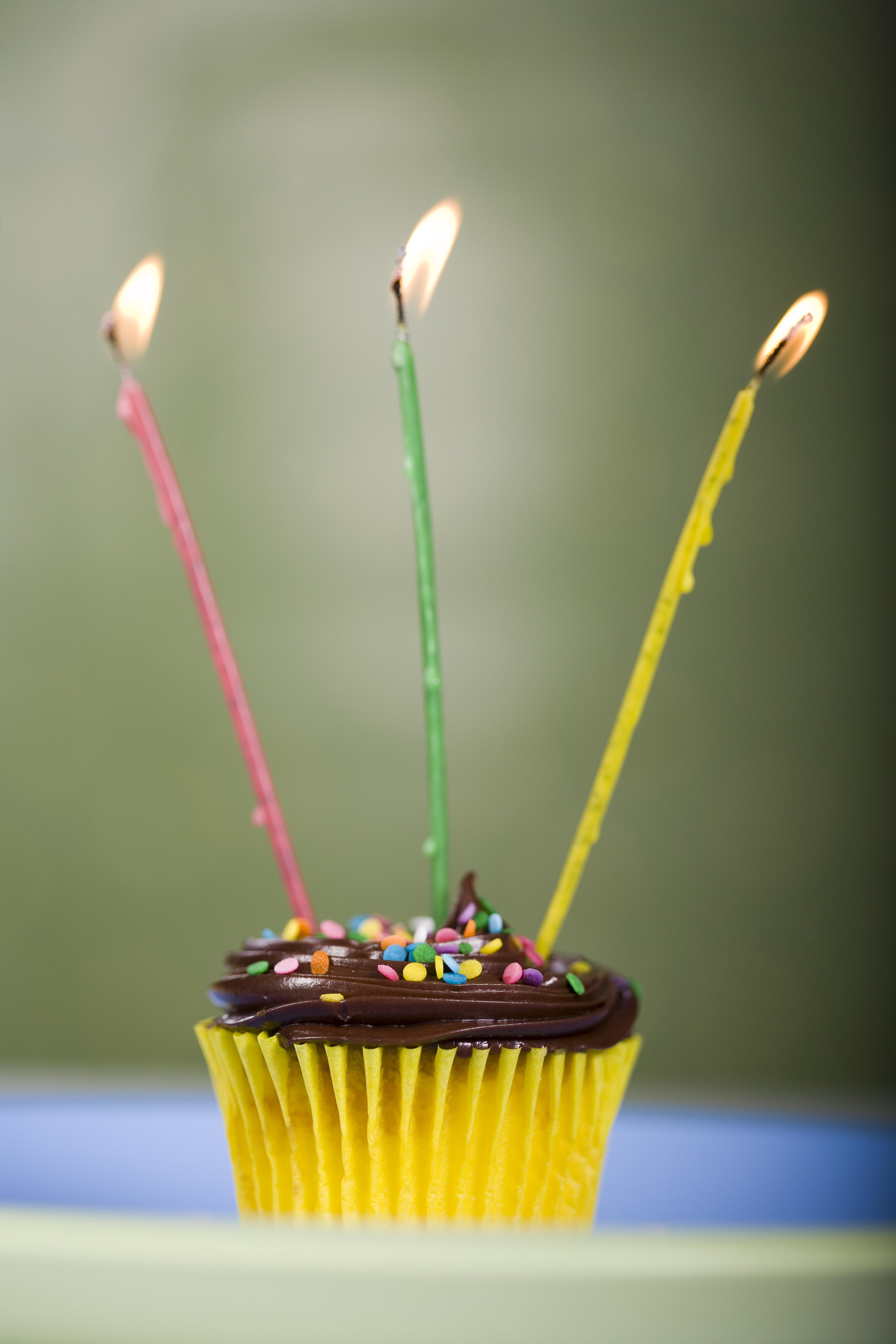 chocolate cupcake with three candles lit