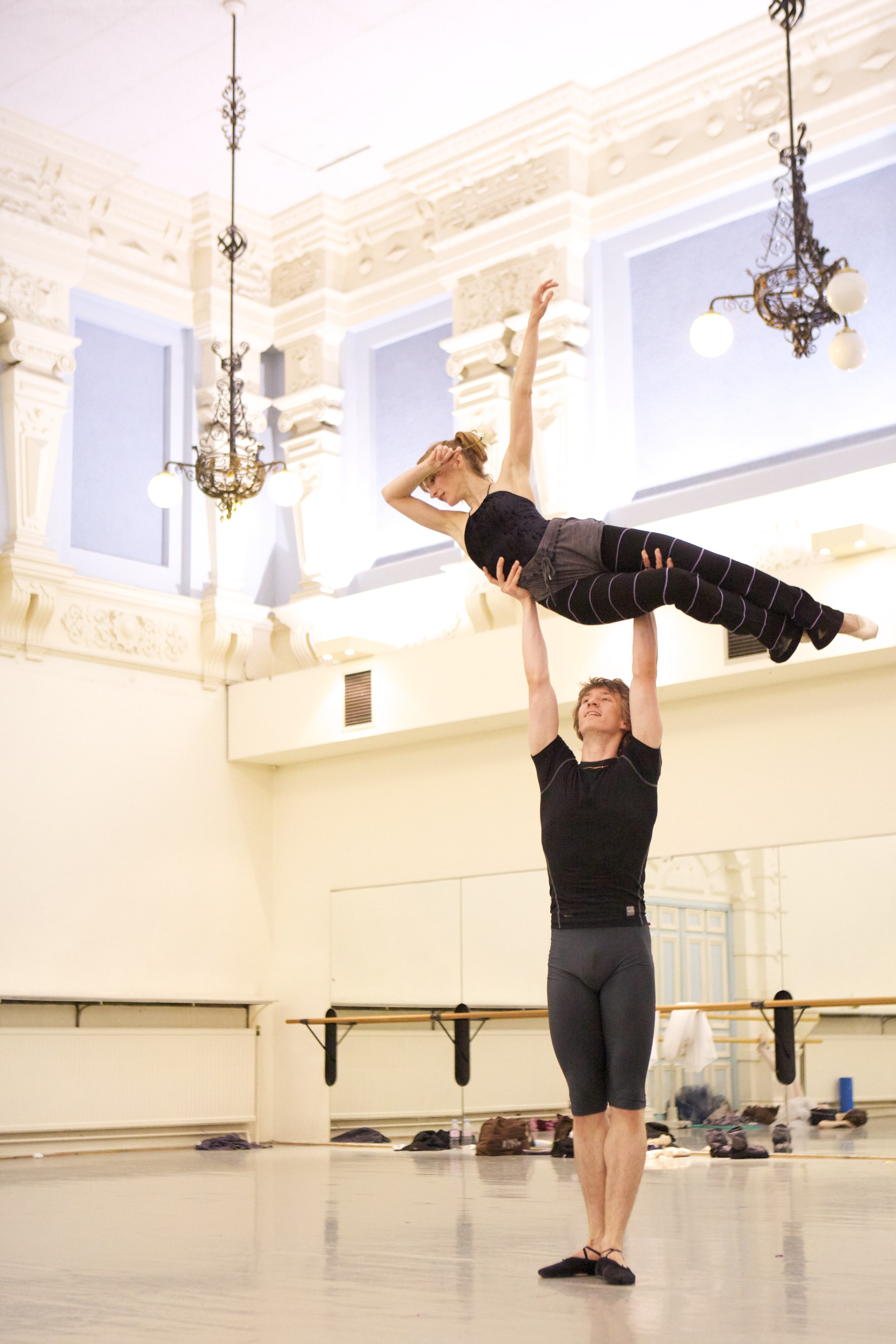 two dancers practice a high lift