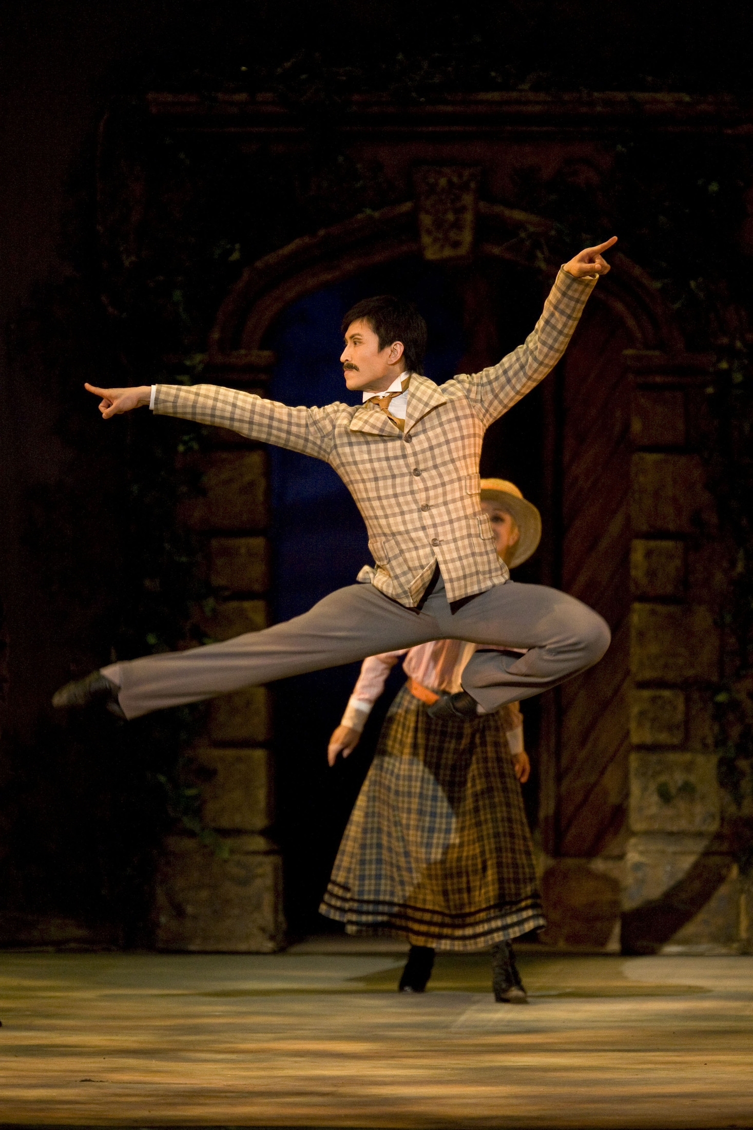 male ballet dancer jumps very high on stage