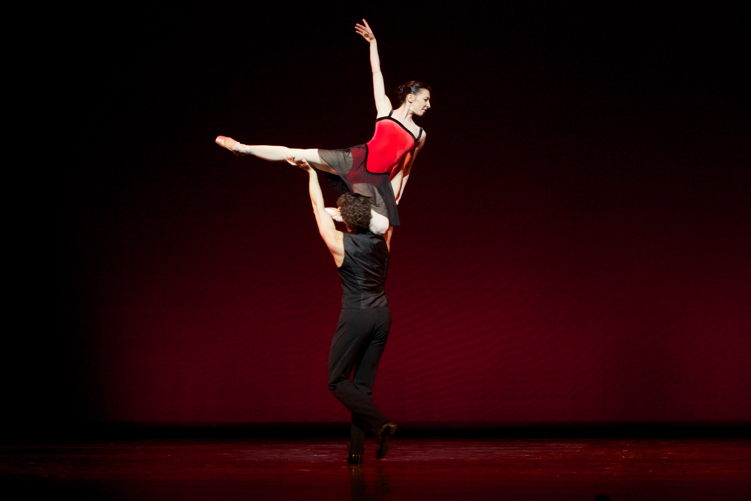 two dancers perform a high ballet lift
