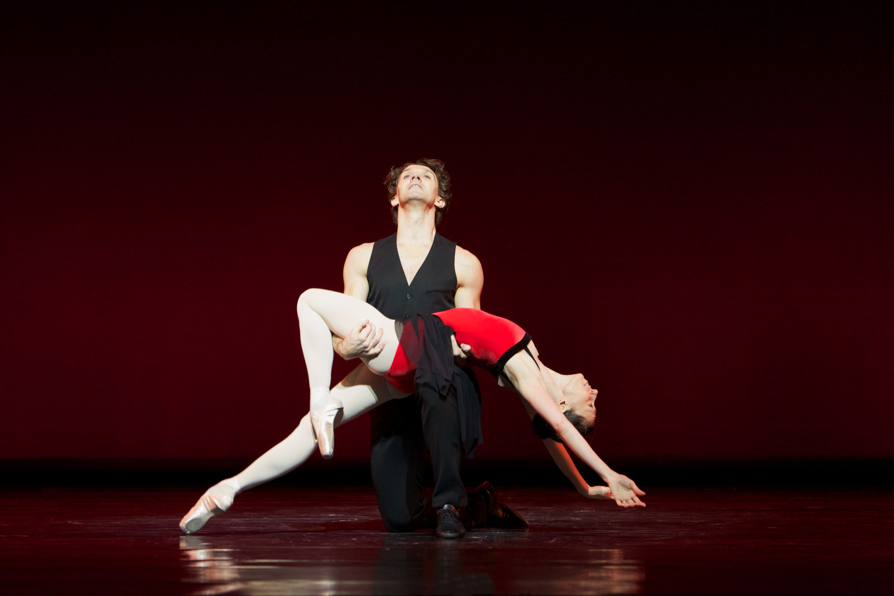 ballet dancers lie on top of one another on stage