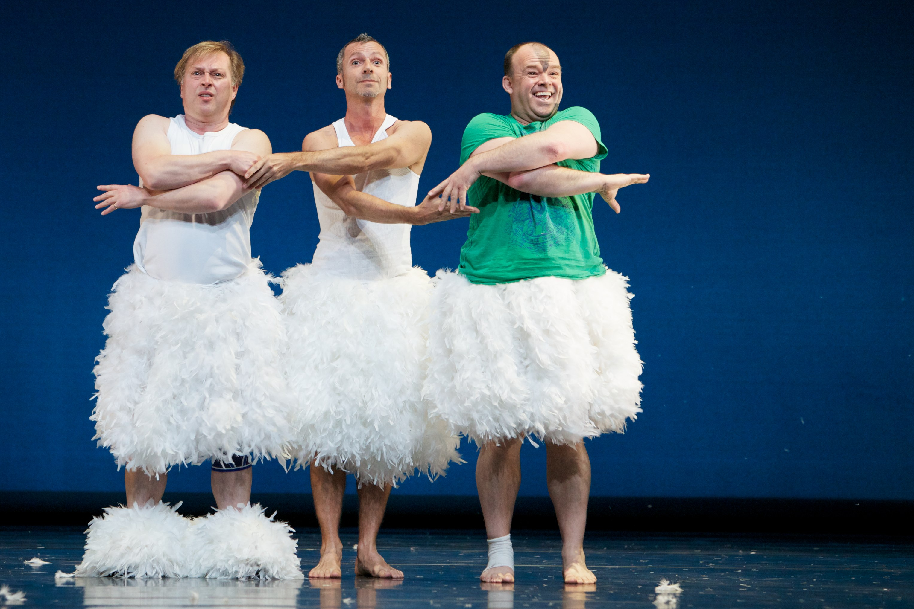 three dancers on stage in white tutus