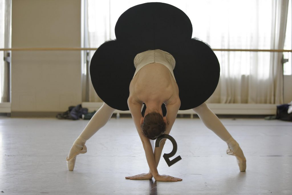 dancer wearing a black card shaped tutu for Alice bends forwards