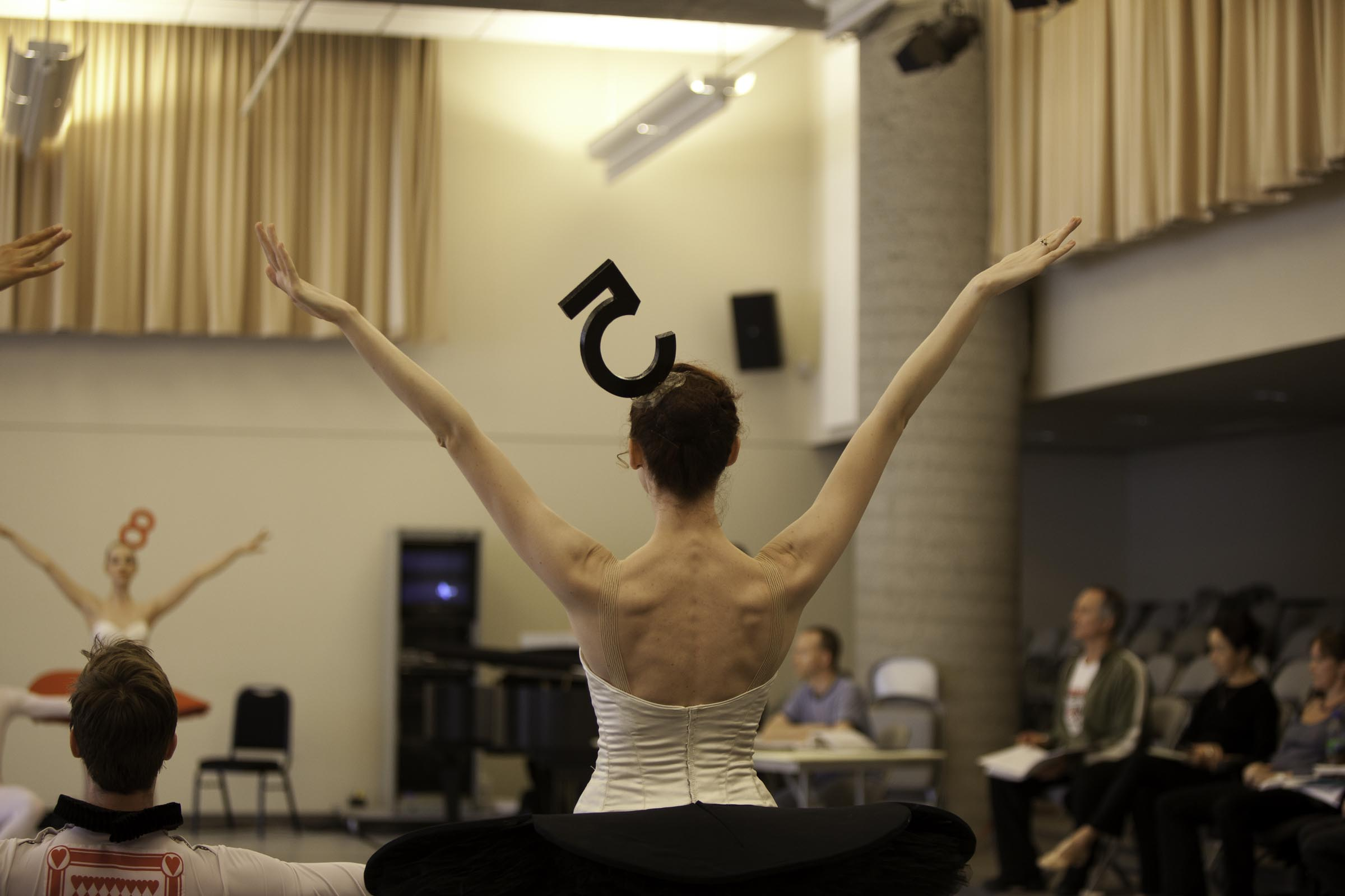dancer raises her arms in rehearsal with her back to the camera