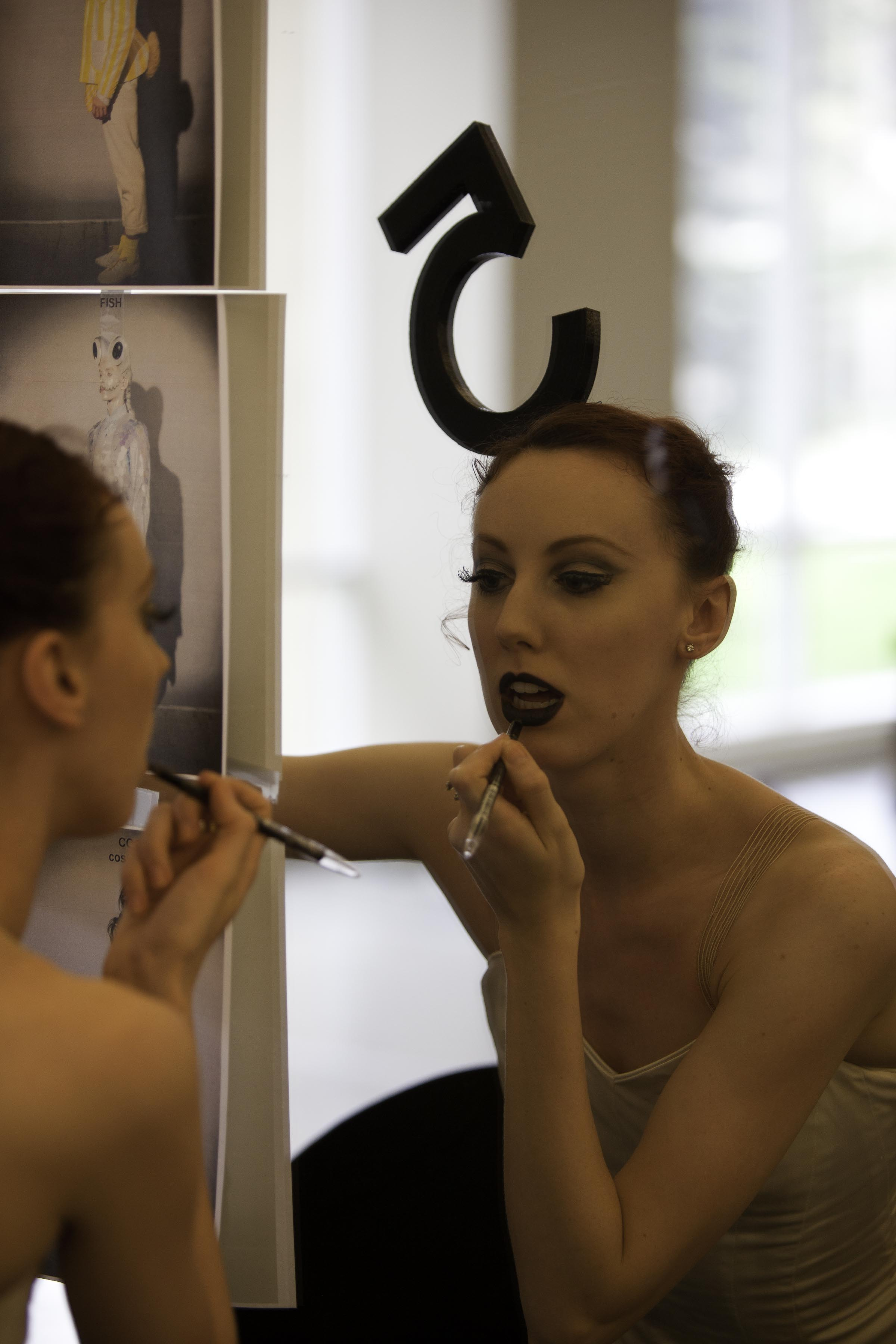 dancer puts on her make-up in front of the mirror