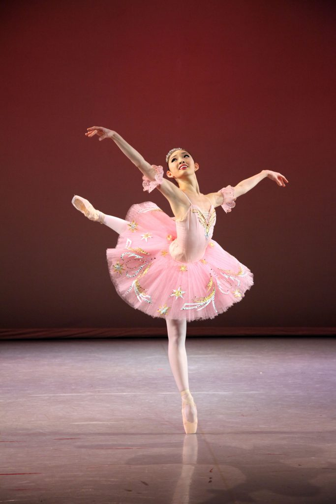 dancer in a pink tutu on pointe on the stage
