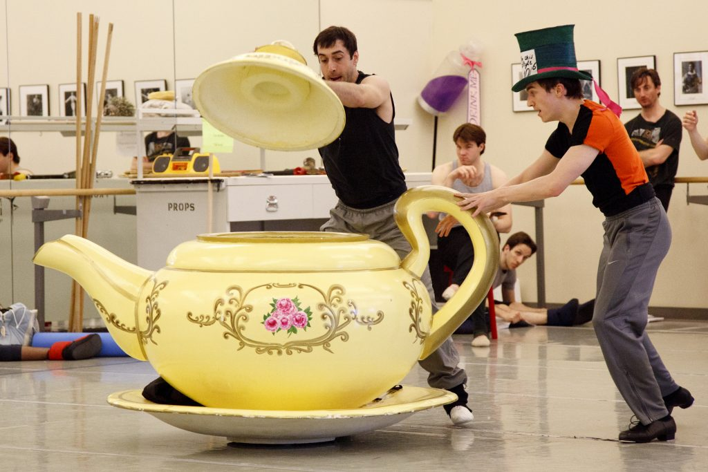 a giant tea cup being moved around by ballet dancers