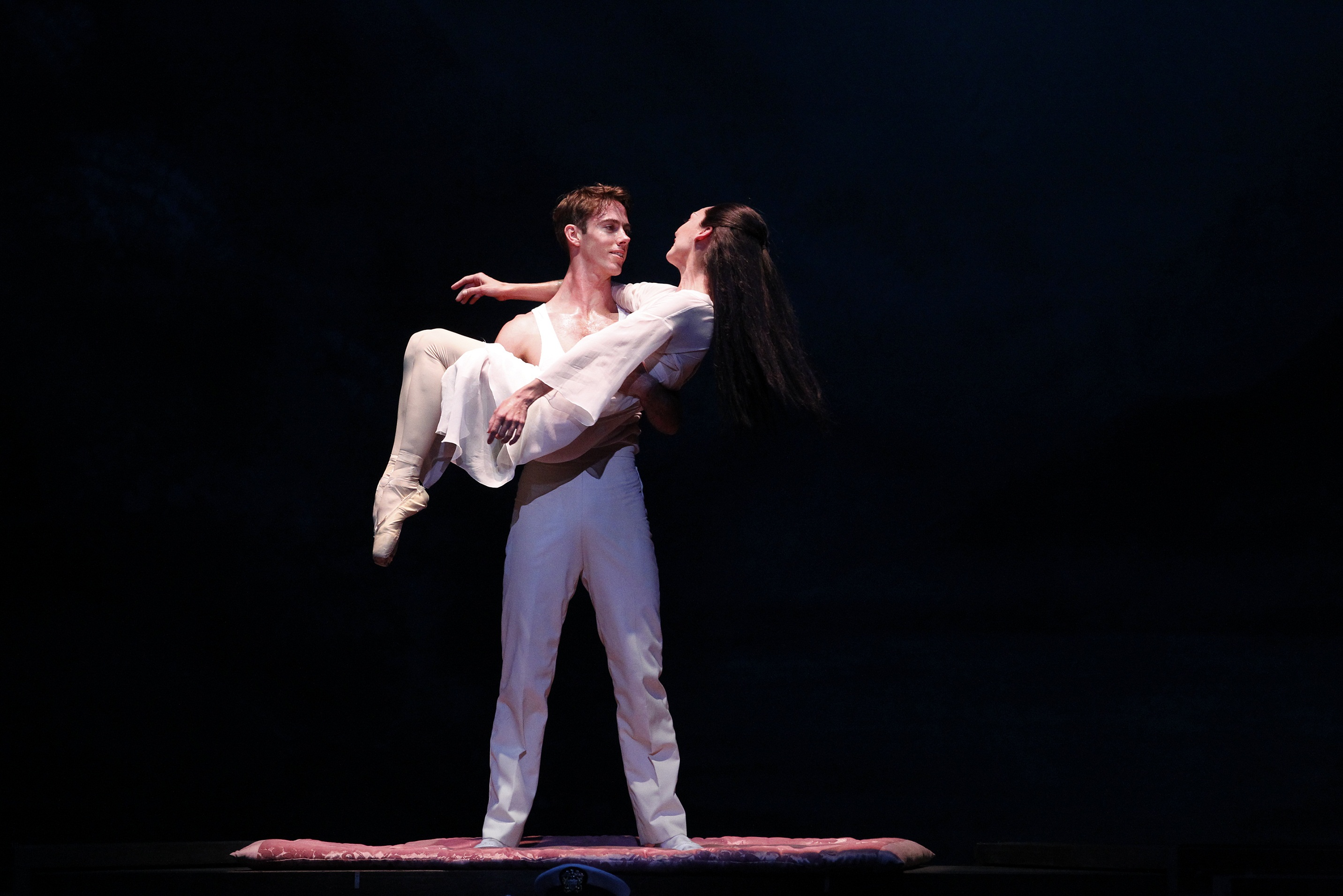 one male ballet dancer holds another female dancer in his arms on stage