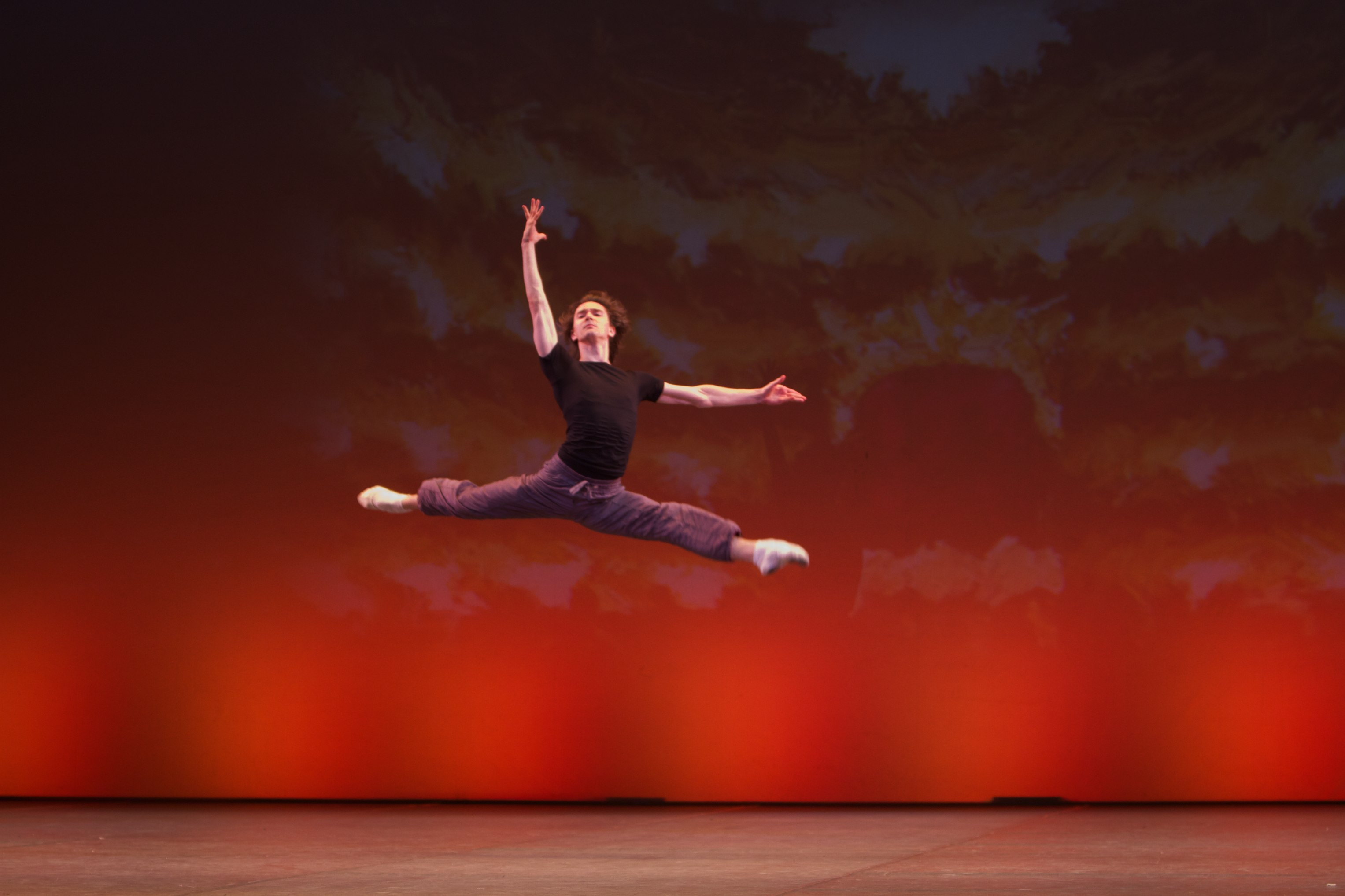 dancer jumps across the stage in a ballet