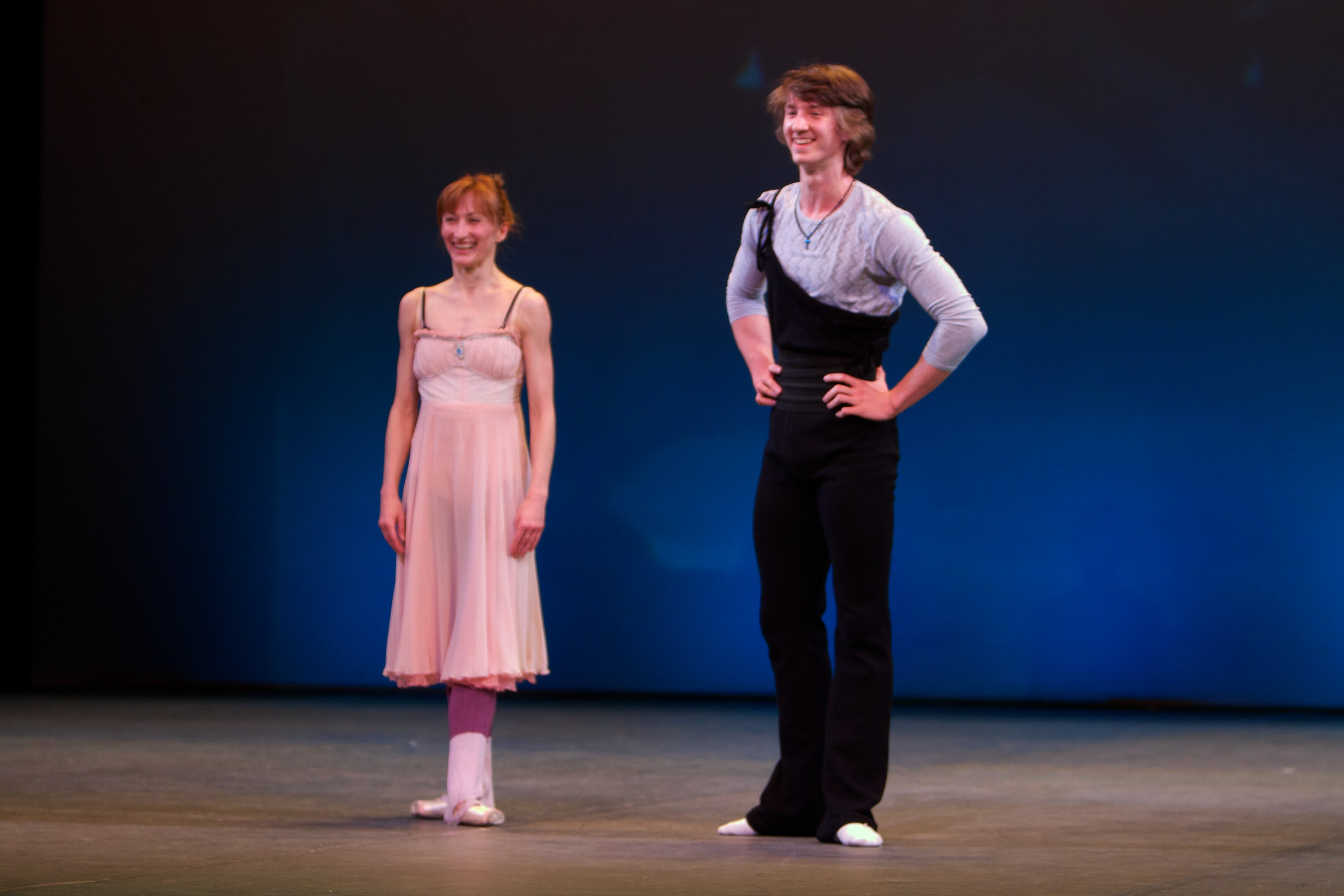 two ballet dancers stand on stage