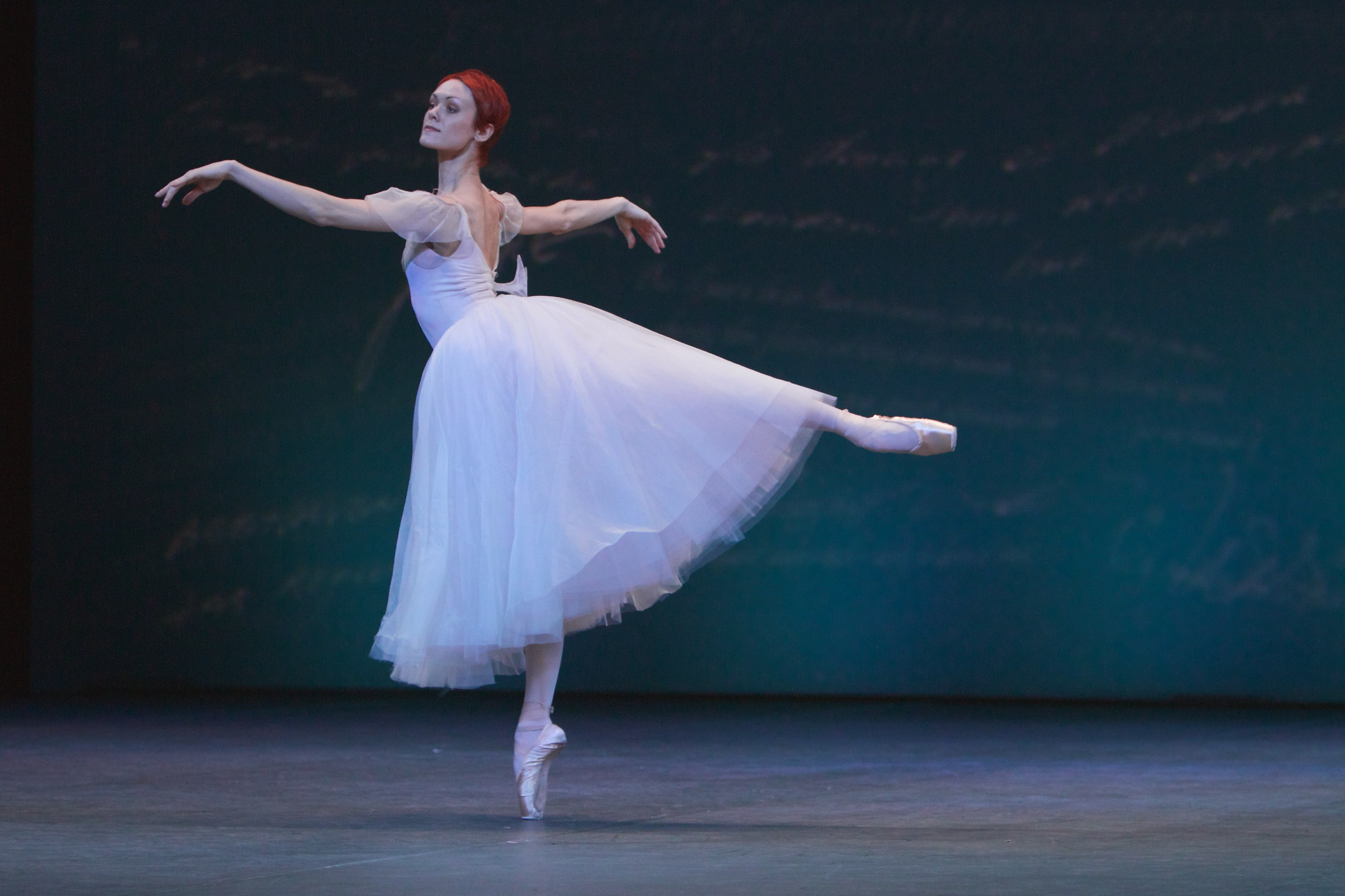 ballet dancer stands on pointe shoe in long white dress