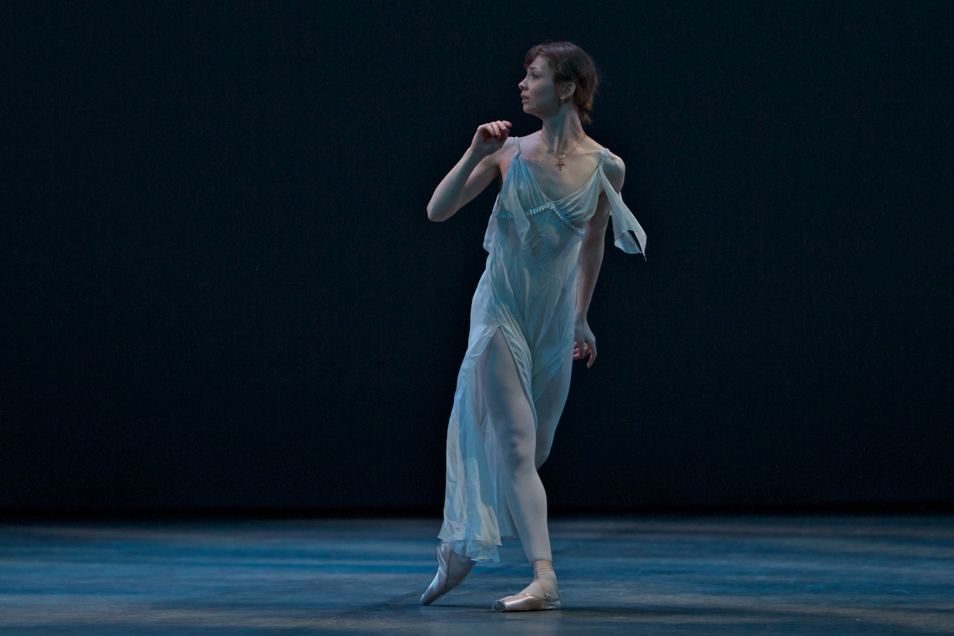 ballet dancers runs across the stage in long white dress