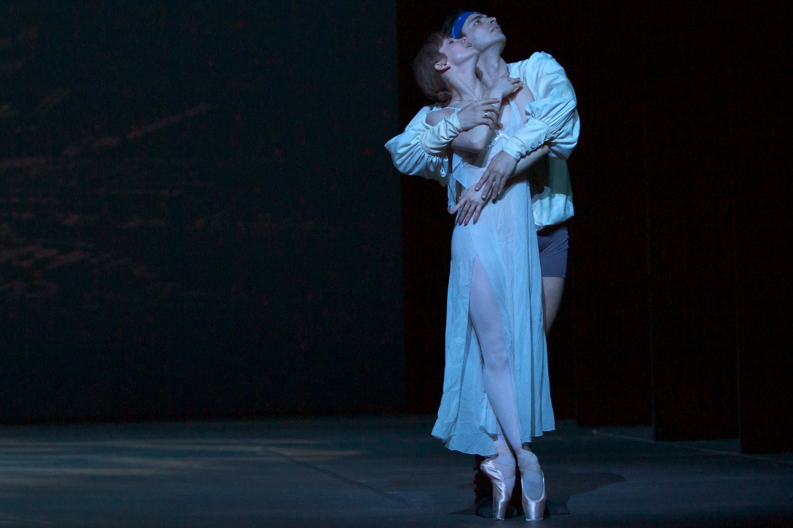 two ballet dancers on stage holding each other