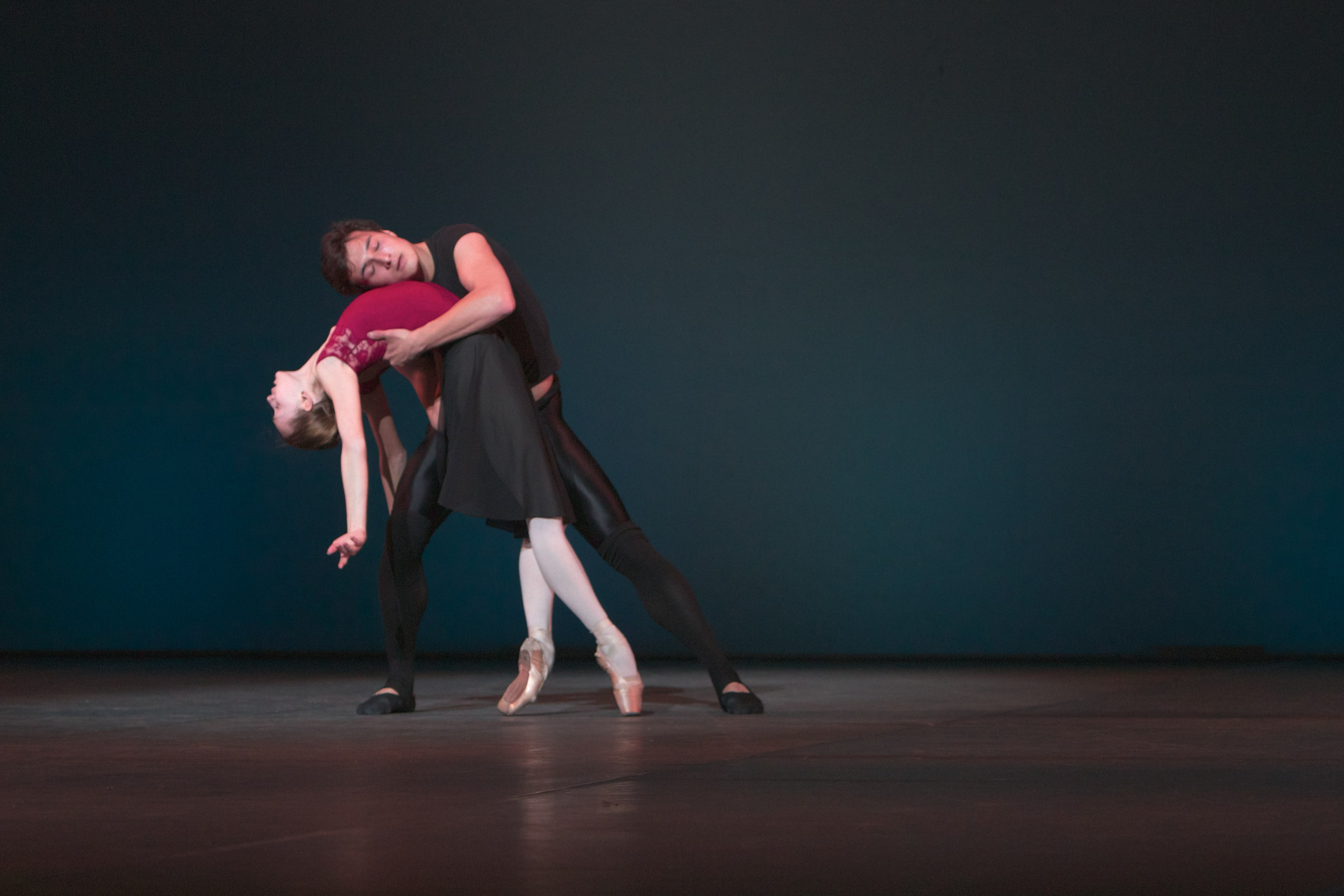 two ballet dancers hold each other on stage