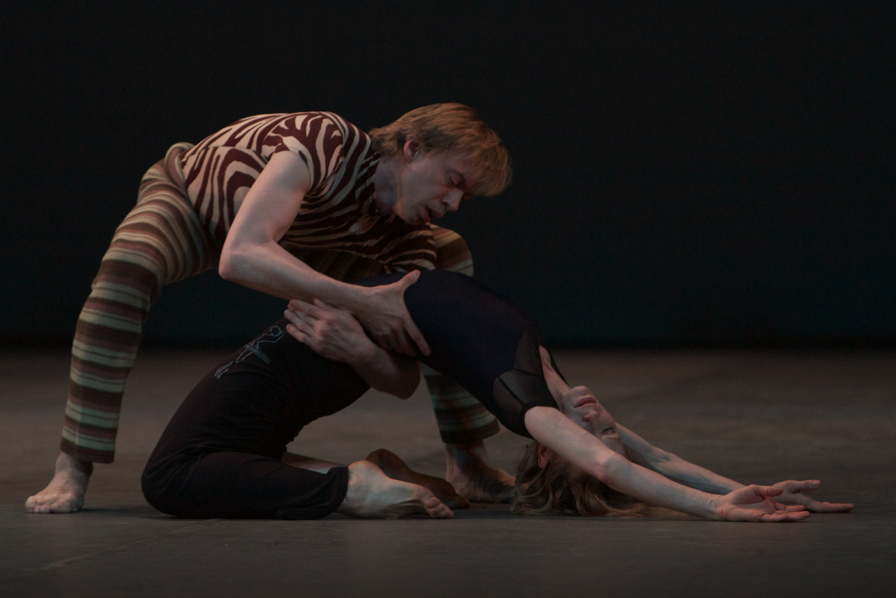 two dancers crouched on stage