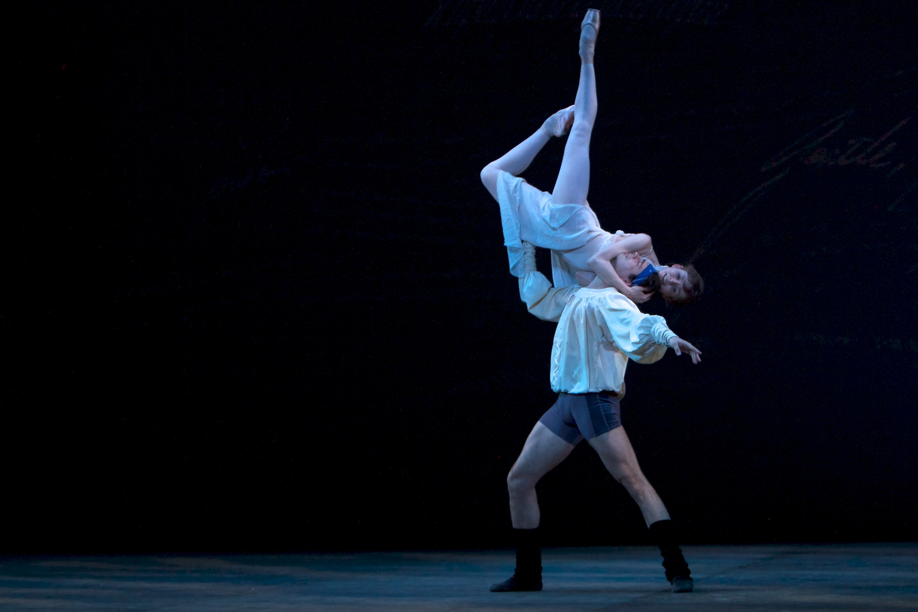 one ballet dancer holds another very high on stage