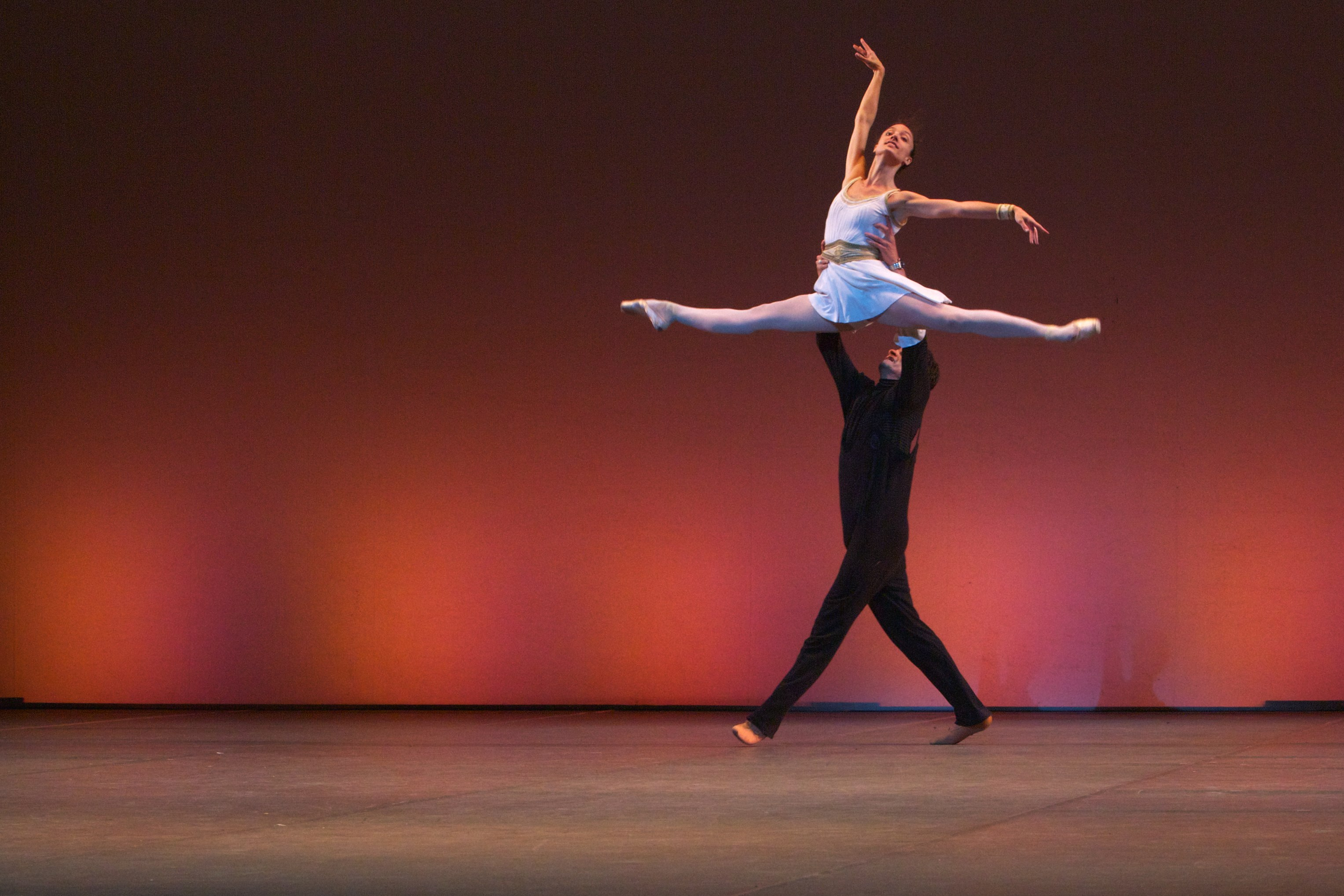 one ballet dancer lifts another very high on stage