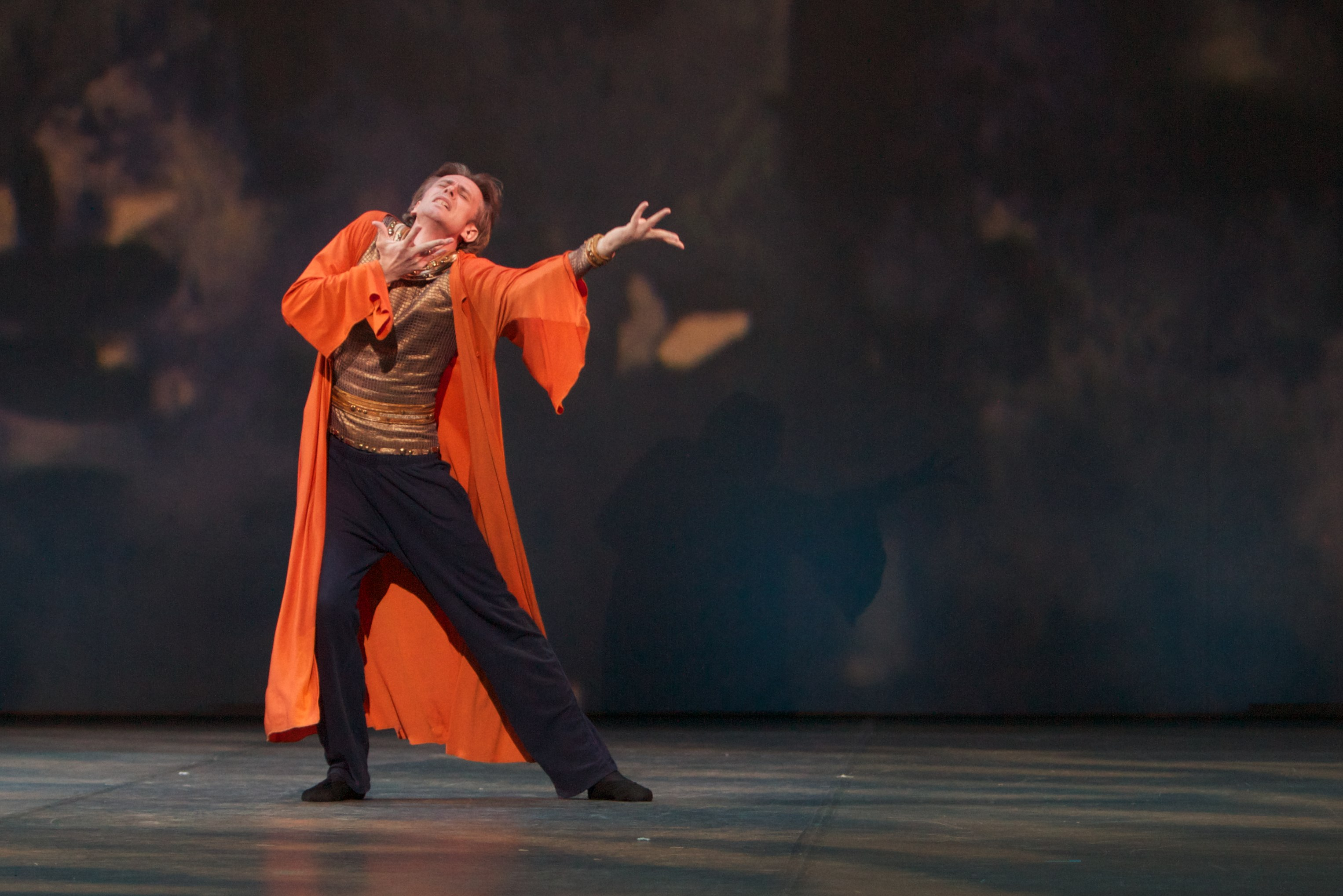 dancer in an orange cloak stands on stage