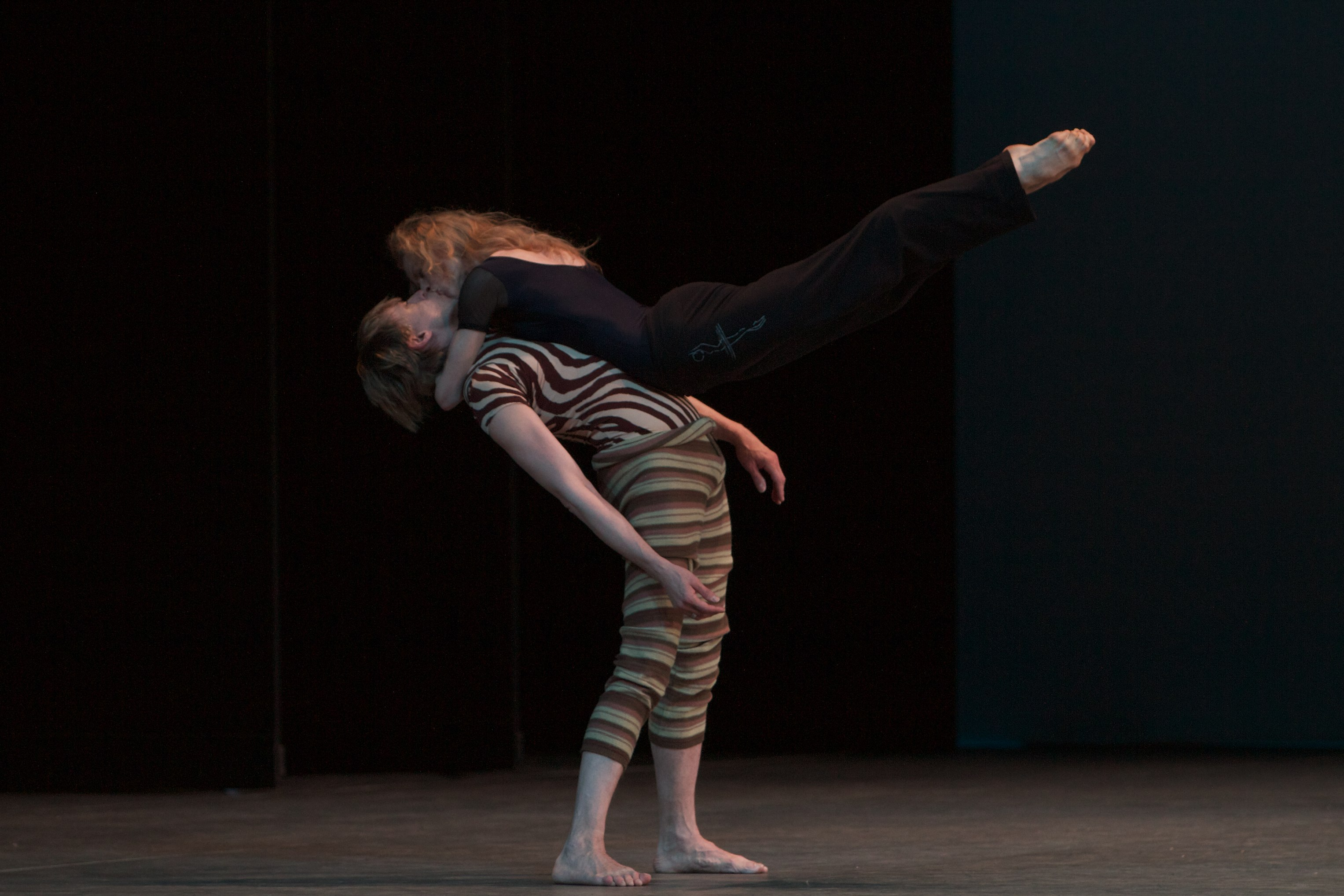 one dancer holds onto the neck of another