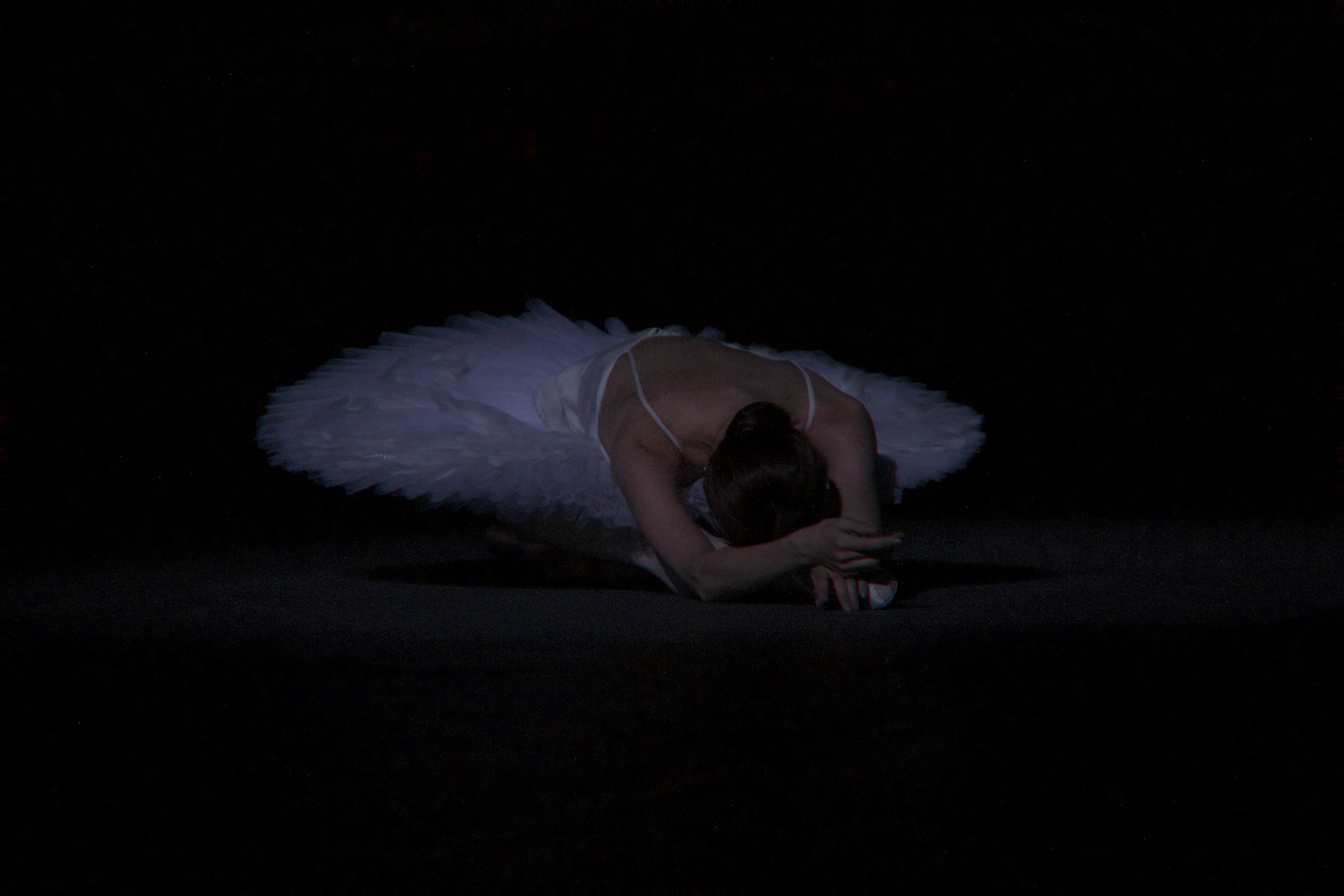 dancer lies on stage like a swan