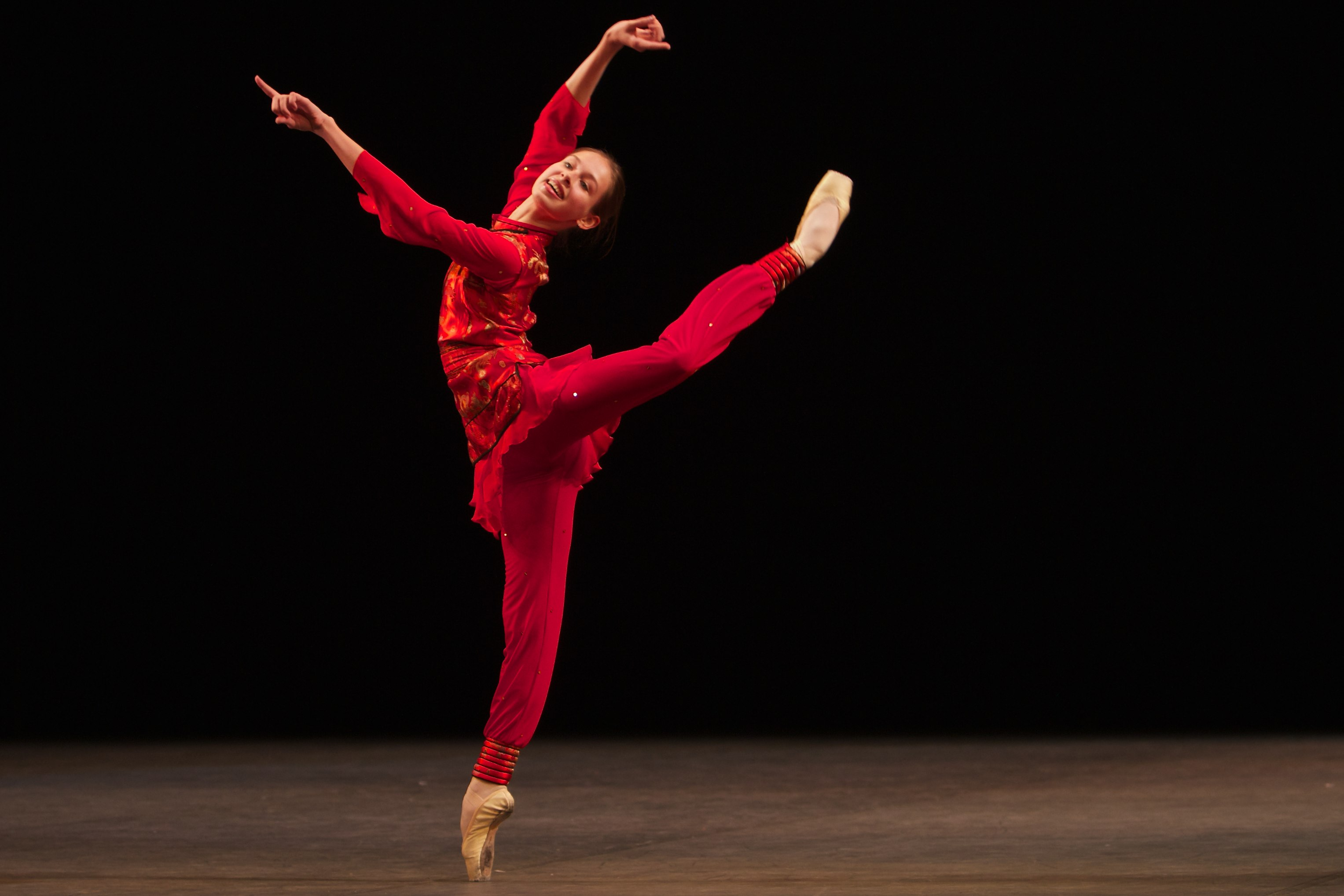 dancer stands on pointe in a red costume