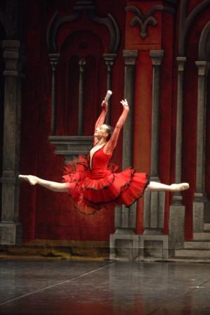 dancer in red dress in a jete on stage
