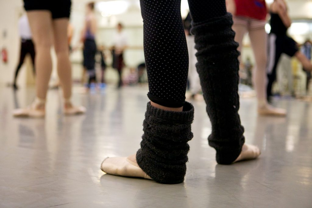 dancer stands in legwarmers and point shoes