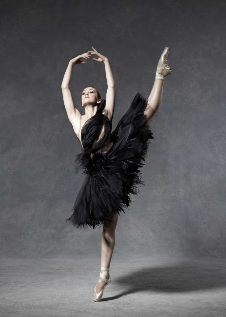 dancer stands on pointe with one leg in the air