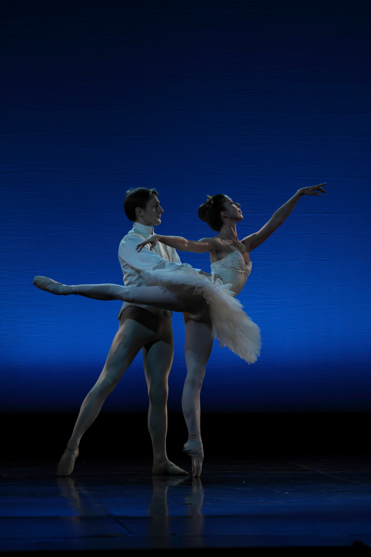 two ballet dancers in white on stage