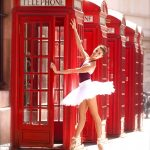 ballet dancer in front of red phone boxes