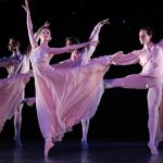 ballet dancers in purple dresses on pointe