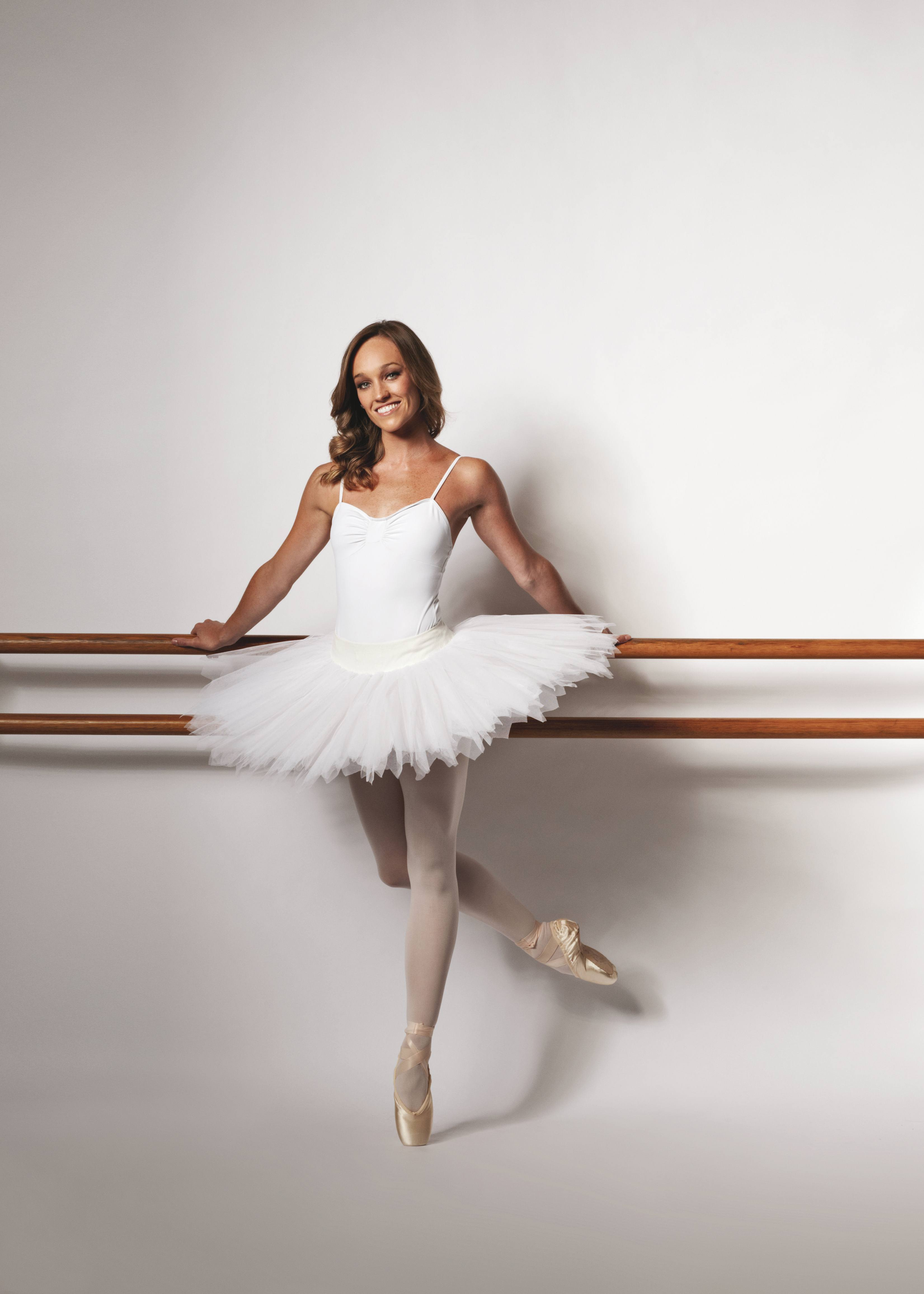 ballet dancer stands at the barre in white tutu