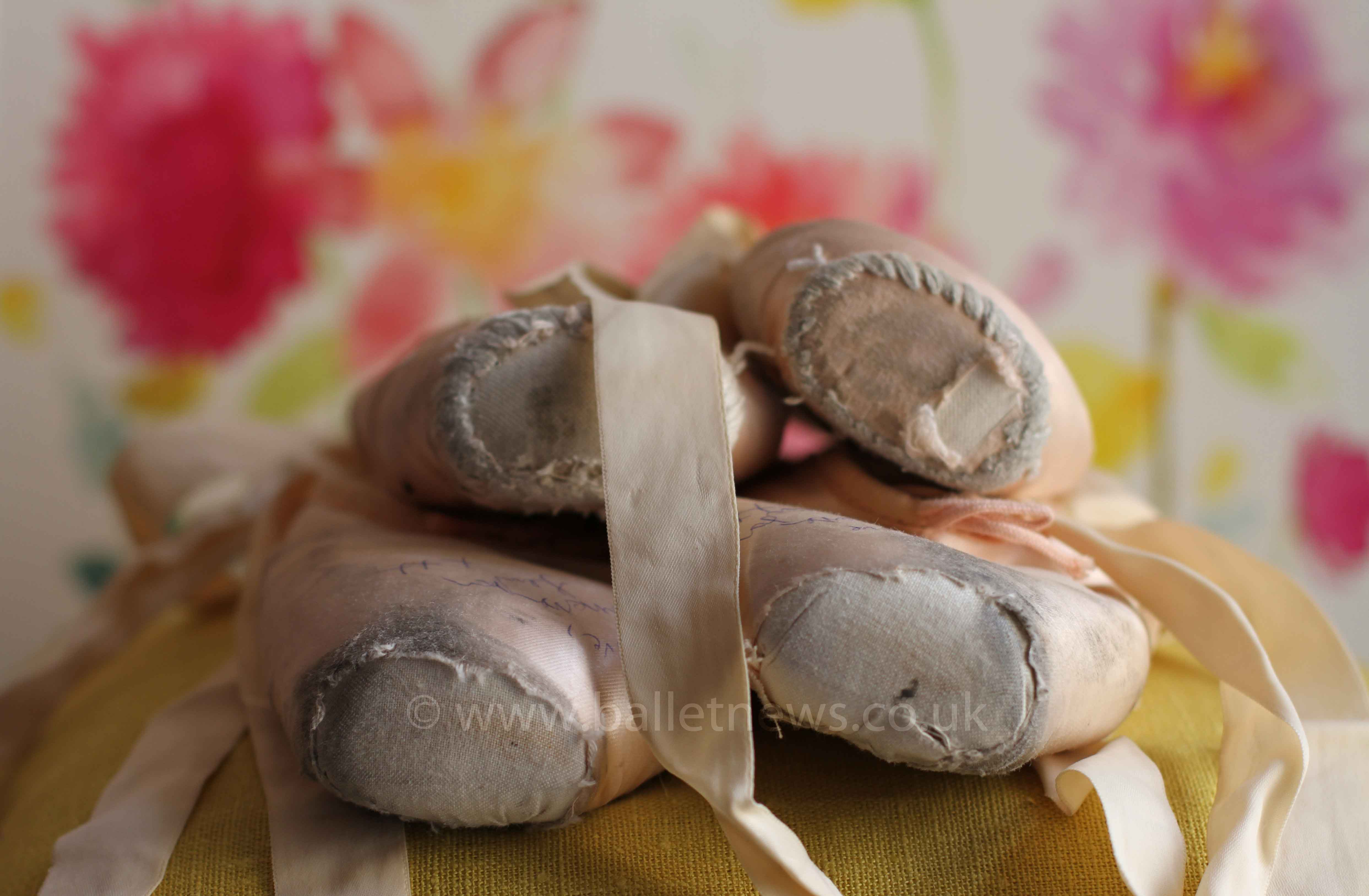 ballet pointe shoes in a pile on a yellow cushion