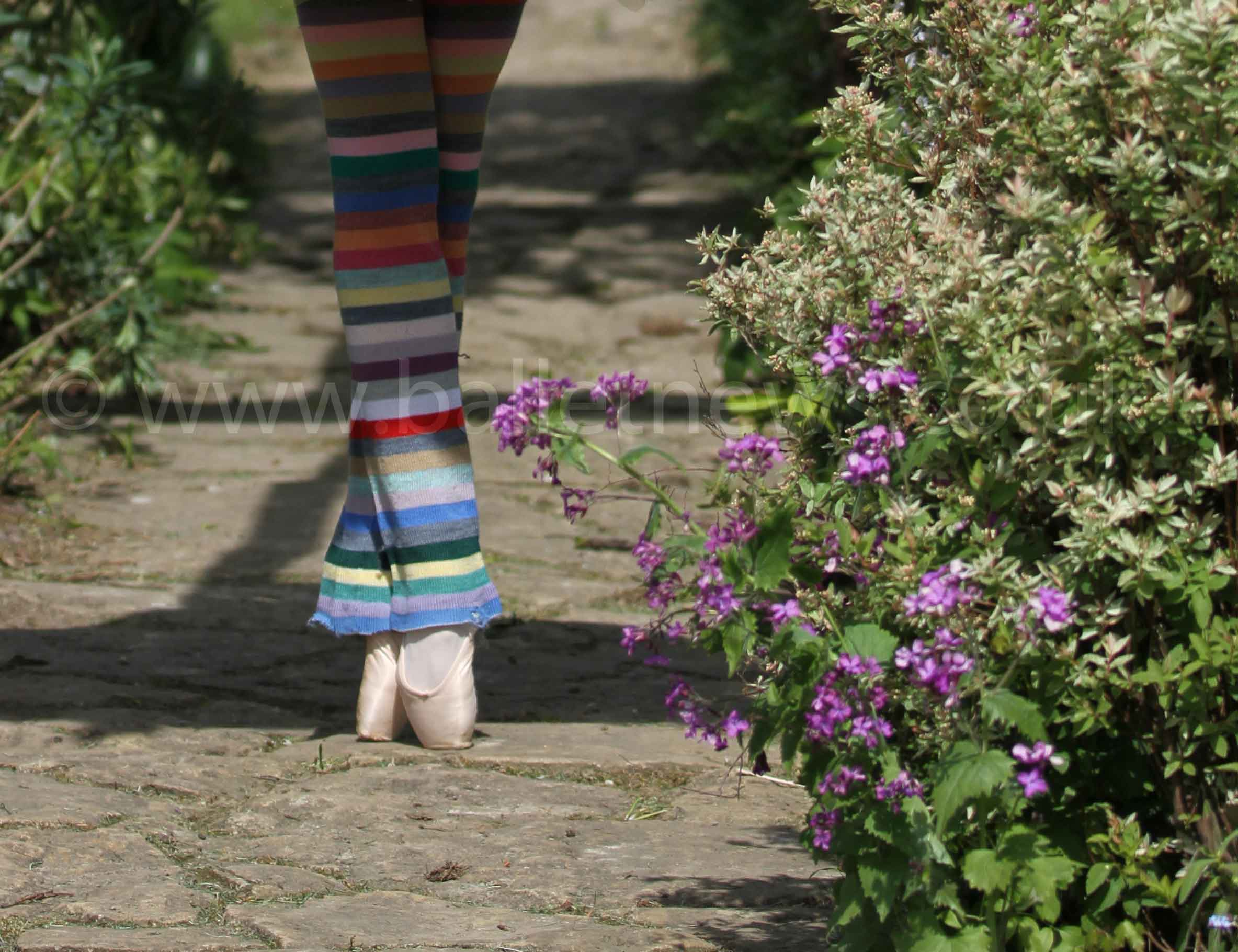 a ballet dancer wears stripy legwarmers and pointe shoes